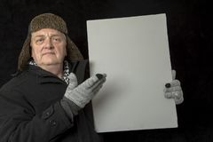 Portrait of a mature man protesting with a plain grey board on a black background. Portrait of a mature man protesting with a plain grey board Royalty Free Stock Image