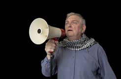 Portrait of a mature man protesting shouting through a megaphone. On a black background Stock Photo