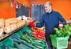 Portrait of mature  man purchasing seasonal veggies in farm food. Portrait of mature cheerful positive man purchasing seasonal veggies in farm food store Stock Photo