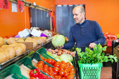 Portrait of mature  man purchasing seasonal veggies in farm food. Portrait of mature smiling  man purchasing seasonal veggies in farm food store Stock Photography