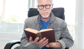 Portrait of mature man reading a book. At home Stock Images