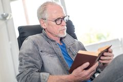 Portrait of mature man reading a book. At home Royalty Free Stock Photography