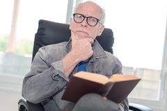 Portrait of mature man reading a book. At home Royalty Free Stock Photos