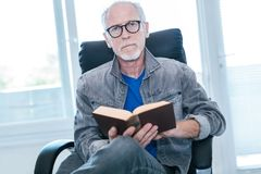 Portrait of mature man reading a book. At home Stock Image