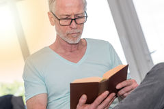 Portrait of mature man reading a book, light effect. Portrait of mature man reading a book at home, light effect royalty free stock photo
