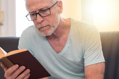 Portrait of mature man reading a book, light effect Stock Photography