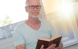 Portrait of mature man reading a book, light effect Stock Images