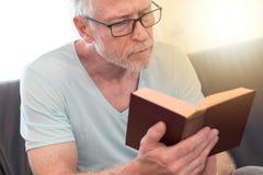 Portrait of mature man reading a book, light effect Stock Photos