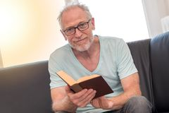 Portrait of mature man reading a book, light effect Royalty Free Stock Photography