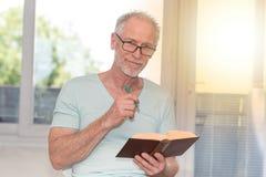 Portrait of mature man reading a book, light effect. Portrait of mature man reading a book at home, light effect Stock Photos