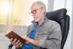 Portrait of mature man reading a book, light effect. Portrait of mature man reading a book at home, light effect Royalty Free Stock Photos