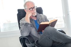 Portrait of mature man reading a book. At home Royalty Free Stock Photo