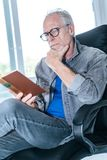 Portrait of mature man reading a book. At home Stock Photography