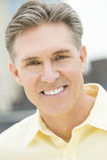 Portrait Of Mature Man Smiling Outdoors. Close-up portrait of happy mature man smiling outdoors Stock Images