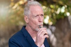 Mature man smoking electronic cigarette outdoors. Portrait of mature man smoking electronic cigarette outdoors Stock Images