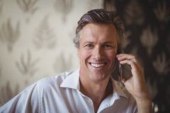 Portrait of mature man talking on mobile phone. In restaurant Royalty Free Stock Photos