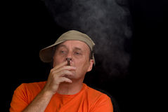 Portrait of mature man wearing baseball cap and smoking cigar Royalty Free Stock Photography