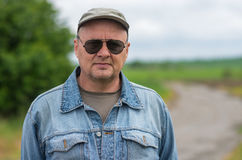 Portrait of mature man wearing hat and black sunglasses Royalty Free Stock Photos