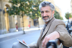 Portrait of mature man websurfing in the streets Royalty Free Stock Image