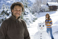 Portrait of mature man in winter setting, woman with snowman in background royalty free stock image
