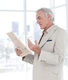 Portrait of a mature manager reading newspaper Stock Image