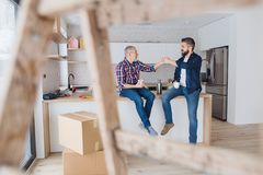 A mature man with his senior father furnishing new house, a new home concept. stock photography