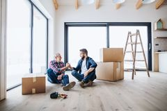 A mature man with his senior father furnishing new house, a new home concept. A portrait of mature men with his senior father shaking hands when furnishing new stock photography