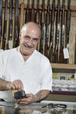 Portrait of a mature merchant with credit card reader in gun shop Stock Image