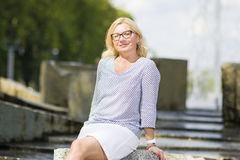 Portrait of Mature Middle Aged smiling Blond Woman Wearing Spectacles Posing Outdoors. Middle Aged Females Concepts. Portrait of Mature Middle Aged smiling Blond Royalty Free Stock Images