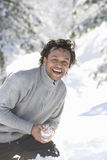 Portrait of mature mixed race man with snowball Royalty Free Stock Photo