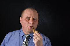 Portrait of mature office clerk smocking tobacco pipe against black background Stock Photos