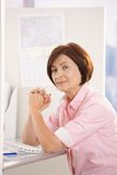 Portrait of mature office worker sitting at desk Stock Image