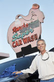Portrait of mature owner of car wash standing below signboard with vehicle Stock Images
