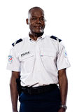 Portrait of mature policeman. Portrait of an afro American mature policeman standing in studio on white isolated background Stock Photo
