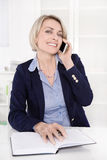 Portrait of a mature or senior business woman flirting on mobile Royalty Free Stock Images