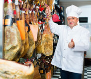 Portrait of mature shop man offering Spanish jamon Royalty Free Stock Images