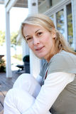 Portrait of mature smiling blond woman in front of home Royalty Free Stock Photo