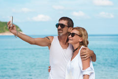 Portrait of mature smiling couple taking a selfie at the beach Royalty Free Stock Images