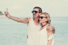 Portrait of mature smiling couple taking a selfie at the beach Stock Image