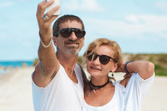 Portrait of mature smiling couple taking a selfie at the beach Stock Photography
