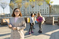 Portrait of mature smiling female teacher in glasses with clipboard, outdor with a group of teenagers students royalty free stock photography