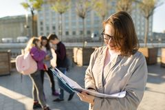 Portrait of mature smiling female teacher in glasses with clipboard, outdor with a group of teenagers students royalty free stock image