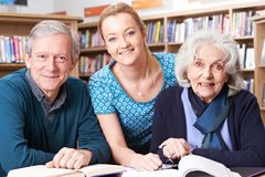Portrait Of Mature Students Working With Teacher In Library Stock Photo