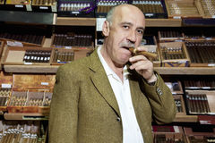 Portrait of mature tobacco shop owner smoking cigar in store Royalty Free Stock Photo