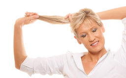 Portrait mature woman blonde holding her long hair Stock Photos