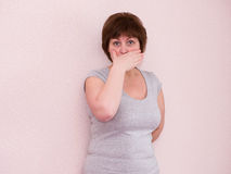 Portrait mature woman covering mouth with hand Stock Photos