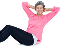 Portrait of mature woman doing sit ups. Over white background Stock Photography