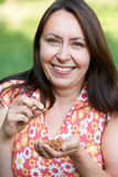 Portrait Of Mature Woman Eating Almonds Stock Image