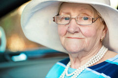 Portrait of a mature woman in glasses and hat sitting in car Royalty Free Stock Image