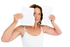Portrait of mature woman holding torn papers. Against white background Stock Photos